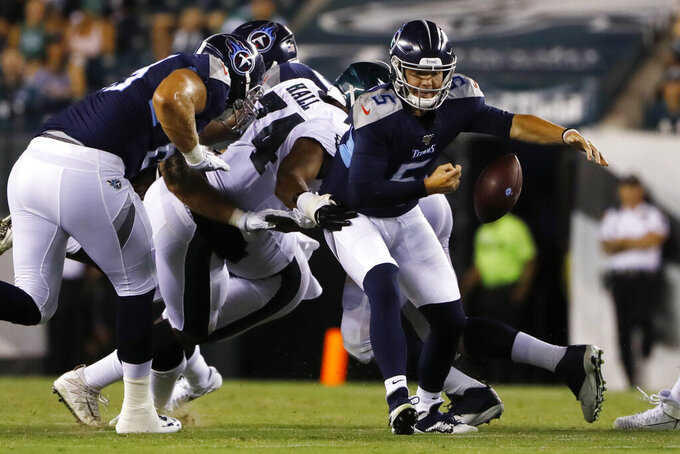 Tennessee Titans' Logan Woodside (5) fumbles the ball as Philadelphia Eagles' Daeshon Hall (74) defends during the second half of a preseason NFL football game Thursday, Aug. 8, 2019, in Philadelphia.(AP Photo/Matt Rourke)