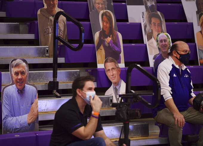 Photographers sit among photo cutouts, including one of Dr. Anthony Fauci, center, in the bleachers behind each basket during an NCAA college basketball game between Holy Cross and BostonMonday, Jan. 4, 2021, in Worcester, Mass. (Christine Peterson/Worcester Telegram & Gazette via AP)
