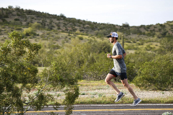 In this April 6, 2018, photo provided by Jimmie Johnson Racing, NASCAR driver Jimmie Johnson runs in Avondale, Ariz. The 83-time winner on the racetrack (sixth-most all-time), Johnson has long been a fitness freak who swam in high school and has run half marathons and triathlons. Johnson plans to run in the Boston Marathon on Monday, April 15. (Bryan Knox/Jimmie Johnson Racing via AP)
