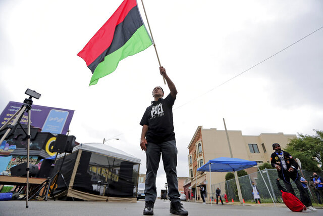 Duncan Ellington waves an African flag during a protest rally for Jacob Blake near Martin Luther King Park on West Vliet Street in Milwaukee, Saturday, Sept. 12, 2020. Blake was shot by police on Aug. 23 as he was being arrested in Kenosha, Wis. (Mike De Sisti/Milwaukee Journal-Sentinel via AP)