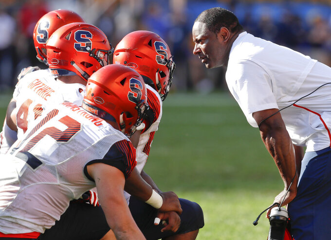 Syracuse head coach Dino Babers, right, talks with his defense during a timeout in the second half of an NCAA football game against Pittsburgh, Saturday, Oct. 6, 2018, in Pittsburgh. Pittsburgh won 44-37 in overtime. (AP Photo/Keith Srakocic)