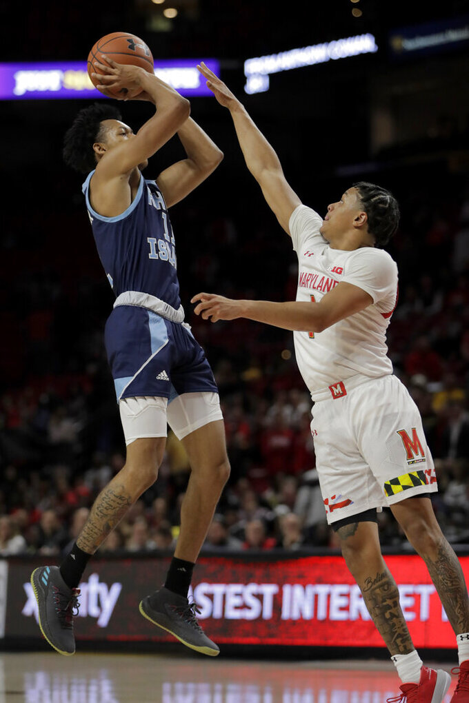 Rhode Island guard Jeff Dowtin, left, shoots against Maryland guard Anthony Cowan Jr. during the second half of an NCAA college basketball game, Saturday, Nov. 9, 2019, in College Park, Md. (AP Photo/Julio Cortez)
