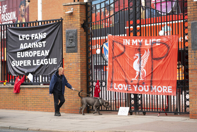 """Banners are seen outside Liverpool's Anfield Stadium after the collapse of English involvement in the proposed European Super League, Liverpool, England, Wednesday, April 21, 2021. Liverpool owner John W Henry has apologised to the club's supporters for the """"disruption"""" caused by the proposed European Super League (ESL). (AP Photo/Jon Super)"""