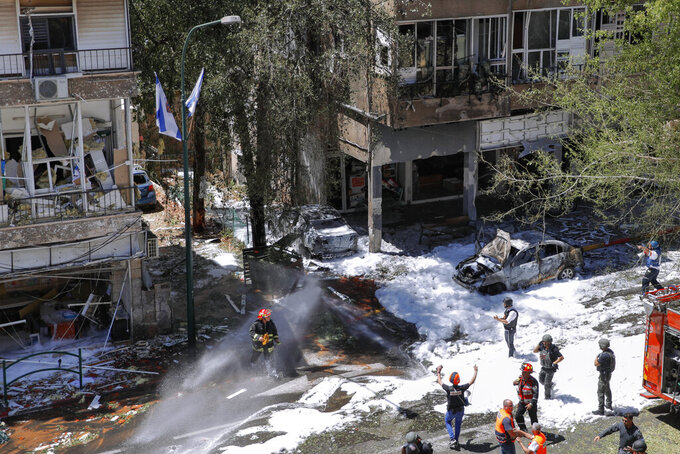 Israeli security forces and emergency services work on a site hit by a rocket fired from the Gaza Strip, in Ramat Gan, central Israel, Saturday, May 15, 2021. (AP Photo/Oded Balilty)