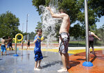 Robbie Marks (right) plays in a splash pad with his son, 6-year-old Raiden Marks at Whiteside Park in Tulsa, Okla., on Monday, August 12, 2019. (Matt Barnard/Tulsa World via AP)