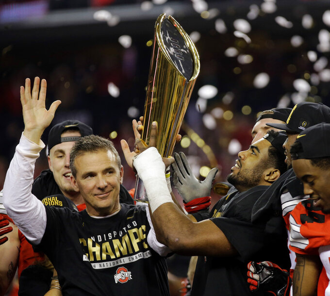 FILE - This Jan. 12, 2015, file photo shows Ohio State head coach Urban Meyer and Ezekiel Elliott celebrating after the NCAA college football playoff championship game against Oregon, in Arlington, Texas. Meyer, the highly successful coach who won three national championships and sparked controversy and criticism this season for his handling of domestic violence allegations against a now-fired assistant, will retire after the Rose Bowl, the university announced Tuesday, Dec. 4, 2018. (AP Photo/Eric Gay, File)