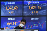 A currency trader watches monitors at the foreign exchange dealing room of the KEB Hana Bank headquarters in Seoul, South Korea, Thursday, Oct. 14, 2021. Asian shares were mostly higher on Thursday, tracking an overnight rally on Wall Street as investors sought out bargains, including technology stocks.(AP Photo/Ahn Young-joon)