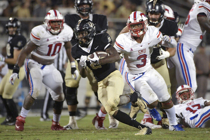 Central Florida running back Otis Anderson, center, breaks free for a 30-yard rushing touchdown past SMU defensive tackle Demerick Gary (10) and linebacker Delano Robinson (3) during the second half of an NCAA college football game Saturday, Oct. 6, 2018, in Orlando, Fla. UCF won 48-20. (AP Photo/Phelan M. Ebenhack)