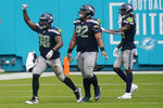 Seattle Seahawks defensive end Alton Robinson (98) celebrates after his tackle against Miami Dolphins running back Myles Gaskin (37) forced a field goal, during the second half of an NFL football game, Sunday, Oct. 4, 2020, in Miami Gardens, Fla. (AP Photo/Lynne Sladky)