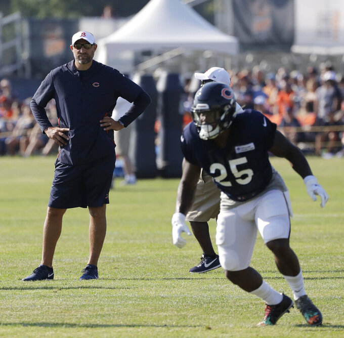 Chicago Bears head coach Matt Nagy, left, watches running back Mike Davis (25) during an NFL football training camp in Bourbonnais, Ill., Sunday, July 28, 2019. (AP Photo/Nam Y. Huh)
