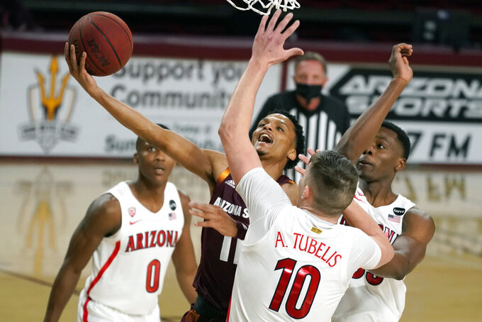 Arizona State guard Alonzo Verge Jr. drives between Arizona's Bennedict Mathurin (0), Azuolas Tubelis (10) and James Akinjo during the first half of an NCAA college basketball game Thursday, Jan. 21, 2021, in Tempe, Ariz. (AP Photo/Rick Scuteri)