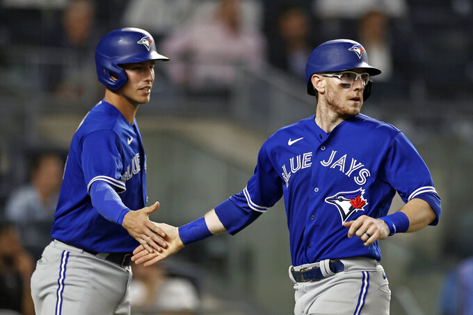 Toronto Blue Jays' Danny Jansen, right, and Jake Lamb celebrate after scoring on a hit by Marcus Semien against the New York Yankees during the fourth inning of a baseball game Wednesday, Sept. 8, 2021, in New York. (AP Photo/Adam Hunger)