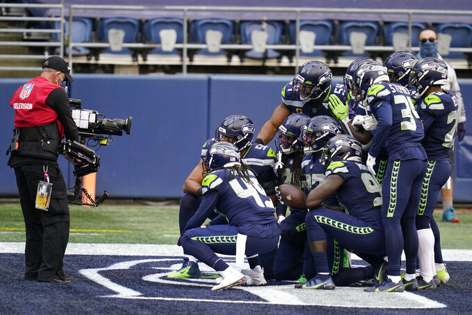 Seattle Seahawks free safety Quandre Diggs (37), center, poses for a photo with teammates after he intercepted a pass against the Los Angeles Rams during the first half of an NFL football game, Sunday, Dec. 27, 2020, in Seattle. (AP Photo/Elaine Thompson)