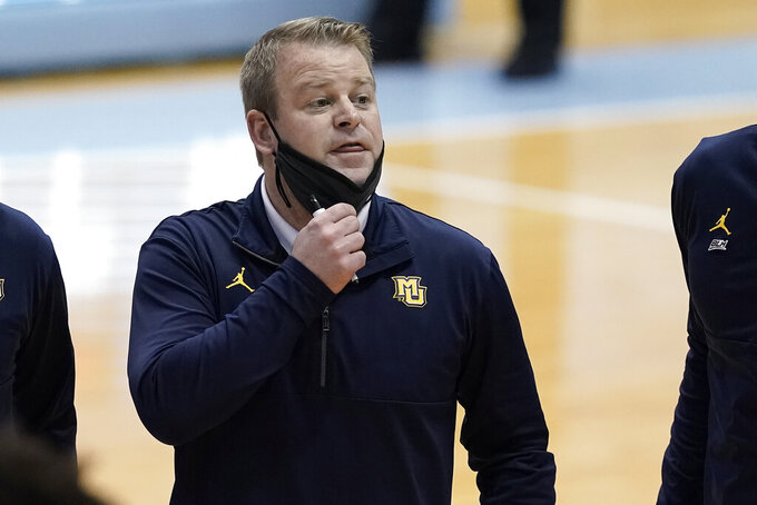 Marquette coach Steve Wojciechowski speaks with players during a timeout in the first half of the team's NCAA college basketball game against North Carolina in Chapel Hill, N.C., Wednesday, Feb. 24, 2021. (AP Photo/Gerry Broome)