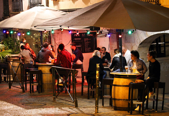 People drink in a bar terrace before the start of a new coronavirus curfew, in Bayonne, southwestern France, Thursday, Oct. 22, 2020. Curfews loom for Italy's three largest cities face new curfews, and similar overnight off-the street rules were decided on Thursday for elsewhere in Europe, including Athens and much of France. (AP Photo/Bob Edme)
