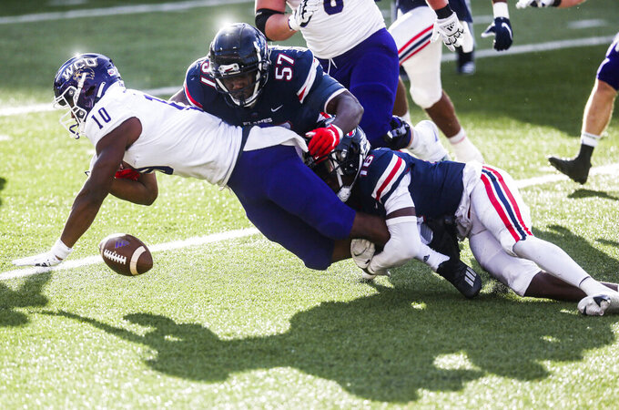 Liberty linebacker Carl Poole (57) gets help from Cornerback Quinton Reese (16) to force Western Carolina running back Malik Richardson (10) to fumble during the second half of an NCAA football game Saturday, Nov. 14, 2020, in Lynchburg, Va. (AP Photo/Shaban Athuman)