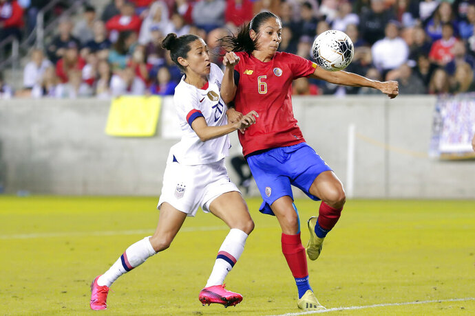 Costa Rica defender Carol Sanchez (6) pushes back on United States forward Christen Press (20) as she brings down the ball during the second half of a Concacaf women's Olympic qualifying soccer match Monday, Feb. 3, 2020, in Houston. (AP Photo/Michael Wyke)