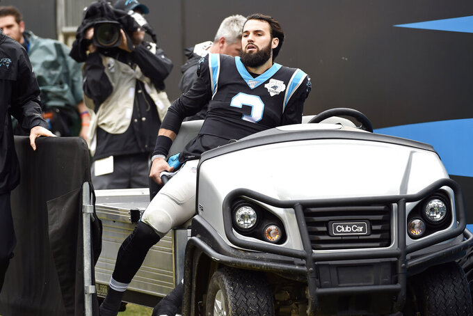 Carolina Panthers quarterback Will Grier (3) is assisted from the field following an injury during the first half of an NFL football game against the New Orleans Saints in Charlotte, N.C., Sunday, Dec. 29, 2019. (AP Photo/Mike McCarn)