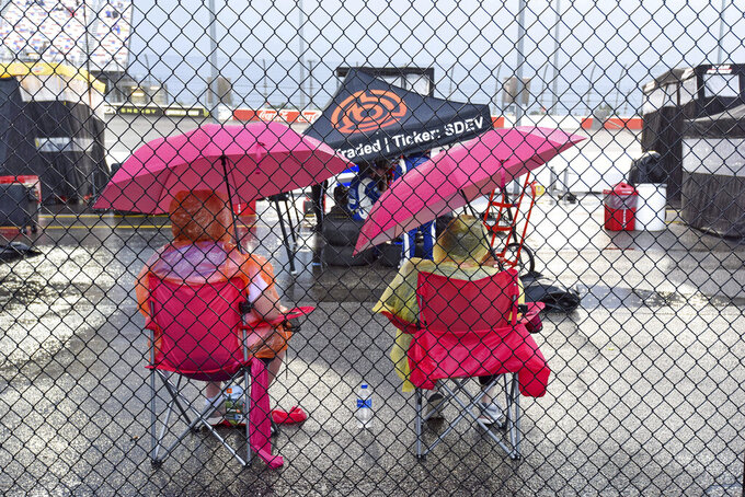 NASCAR fans wait out a rain delay before the start of a NASCAR Cup Series auto race on Sunday, Sept. 1, 2019, at Darlington Raceway in Darlington, S.C. (AP Photo/Richard Shiro)