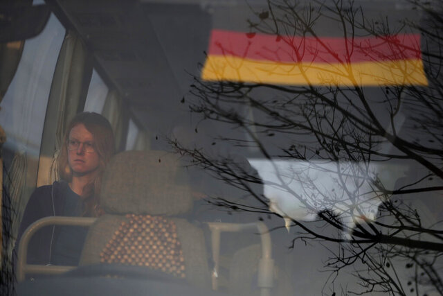A stranded German tourist sits inside a bus taking her to the airport in Kathmandu, Nepal, Friday, March 27, 2020. A rescue flight arranged by the German government on Friday picked up tourists who had been stranded in Nepal since the Himalayan nation went on lockdown earlier this week, officials said. The airport reopened only for the flight, which did not bring any passengers to Nepal. Up to 10,000 tourists are believed to be stranded in Nepal since the government ordered a complete lockdown that halted all flights and road travel to prevent the spread of the virus. (AP Photo/Niranjan Shrestha)
