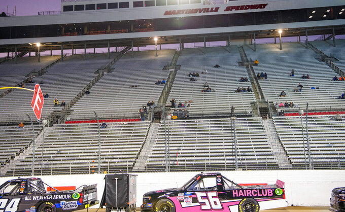 Some of the 1,000 fans allowed in for the NASCAR Truck Series auto race sit in the stands at Martinsville Speedway in Martinsville, Va., Friday, Oct. 30, 2020. (AP Photo Lee Luther Jr.)