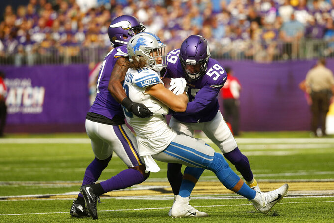 Detroit Lions tight end T.J. Hockenson, center, is tackled by Minnesota Vikings cornerback Patrick Peterson, left, and linebacker Nick Vigil (59) after catching a pass during the first half of an NFL football game, Sunday, Oct. 10, 2021, in Minneapolis. (AP Photo/Bruce Kluckhohn)