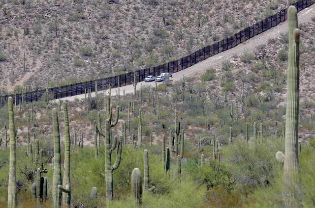 FILE - In this Aug. 22, 2019, file photo, U.S. Customs and Patrol agents sit along a section of the international border wall that runs through Organ Pipe National Monument in Lukeville, Ariz. A public-private project that maps the bodies of border crossers recovered from Arizona's inhospitable deserts, valleys and mountains said this week of Monday, Jan. 4, 2021 that it documented 227 such deaths in 2020, the highest in a decade following the hottest, driest summer in state history. (AP Photo/Matt York, File)