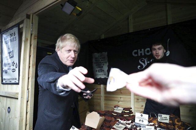 Britain's Prime Minister Boris Johnson visits a Christmas market whilst on the General Election campaign, in Salisbury, England, Tuesday, Dec. 3, 2019. Britain goes to the polls on Dec. 12. (Hannah McKay/Pool Photo via AP)
