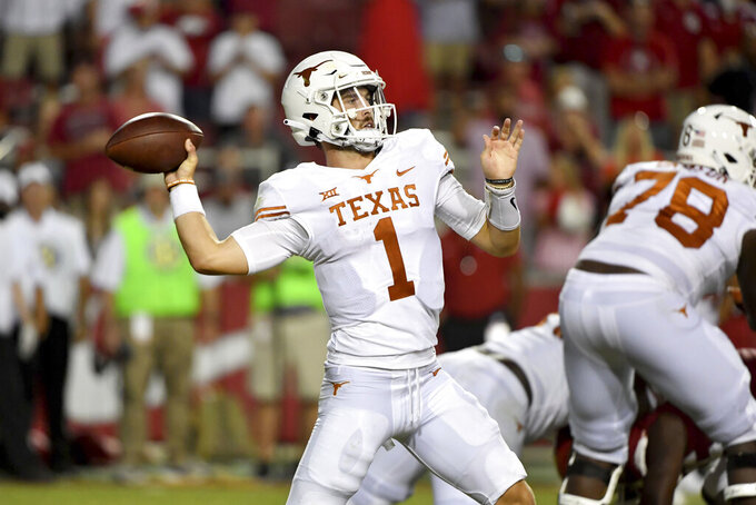 Texas quarterback Hudson Card (1) drops back to pass against Arkansas during the second half of an NCAA college football game Saturday, Sept. 11, 2021, in Fayetteville, Ark. (AP Photo/Michael Woods)