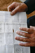In this Monday, May 4, 2020 photo, Halil Hasani shows a document containing names of his four missing sons taken by Serb forces during the Kosovo war two decades ago, as he sits in the porch of his house in the village of Qabra. Hasani is convinced his four sons are alive and imprisoned somewhere in Serbia more than two decades after police and paramilitary forces took them from a village in Kosovo. At the time, an armed uprising by ethnic Albanian separatists had led to a bloody Serb crackdown, an international crisis and a NATO bombing campaign in Kosovo, then a Serbian province.  (AP Photo/Visar Kryeziu)