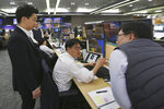 Currency traders work at the foreign exchange dealing room of the KEB Hana Bank headquarters in Seoul, South Korea, Thursday, Dec. 5, 2019.  Asian shares were rising Thursday amid renewed hopes a U.S. trade deal with China may be nearing, despite tough recent talk from President Donald Trump.(AP Photo/Ahn Young-joon)