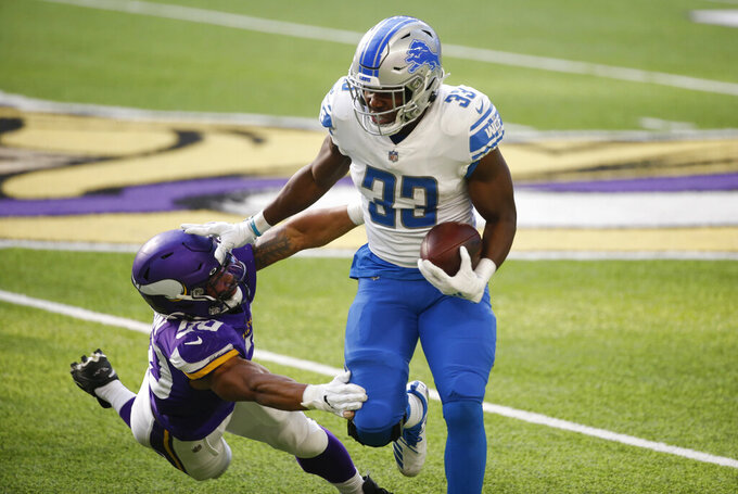 Detroit Lions running back Kerryon Johnson (33) tries to break a tackle by Minnesota Vikings linebacker Eric Wilson, left, during the first half of an NFL football game, Sunday, Nov. 8, 2020, in Minneapolis. (AP Photo/Bruce Kluckhohn)