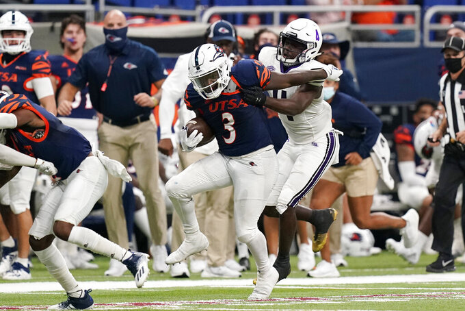 UTSA running back Sincere McCormick (3) tries to break away from Stephen F. Austin cornerback Willie Roberts (4) on a run during the second half of an NCAA college football game, Saturday, Sept. 19, 2020, in San Antonio. (AP Photo/Eric Gay)