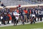 Louisville wide receiver Braden Smith (81) falls into the Virginia team bench during an NCAA college football game Saturday, Nov. 14, 2020, in Charlottesville, Va. (Erin Edgerton/The Daily Progress via AP)