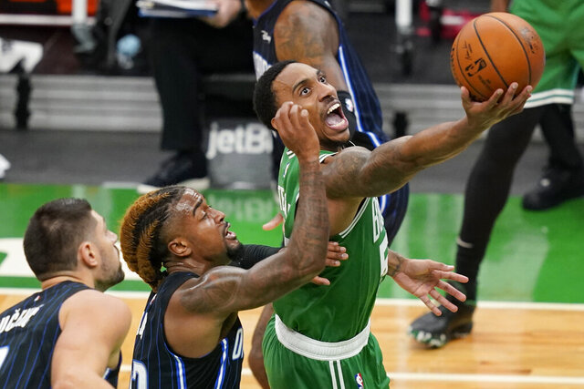 Boston Celtics guard Jeff Teague goes to the basket against the defense of Orlando Magic center Nikola Vucevic, left, and guard Jordan Bone during the first half of an NBA basketball game Friday, Jan. 15, 2021, in Boston. (AP Photo/Elise Amendola)