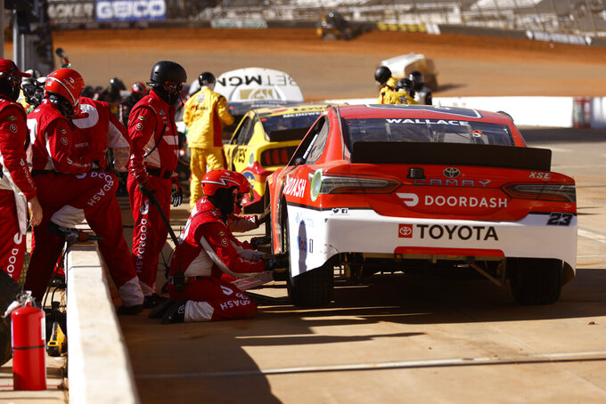 Member of the pit crew for driver Bubba Wallace (23) work on his car during a competition caution of a NASCAR Cup Series auto race, Monday, March 29, 2021, in Bristol, Tenn. (AP Photo/Wade Payne)