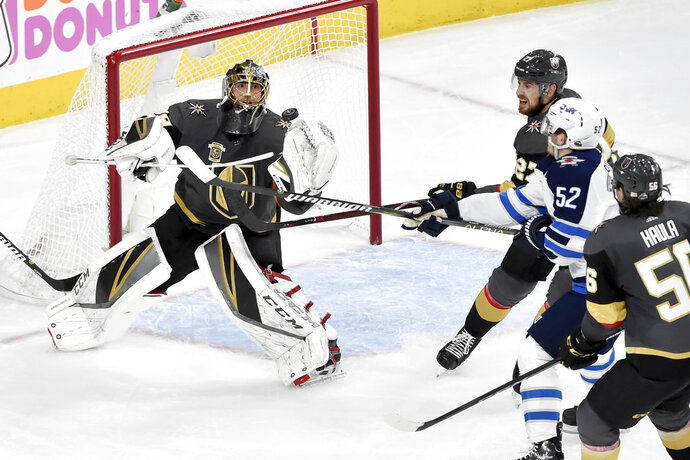 Vegas Golden Knights goaltender Marc-Andre Fleury, left, blocks a shot by Winnipeg Jets center Jack Roslovic during the second period of Game 3 of the NHL hockey playoffs Western Conference finals Wednesday, May 16, 2018, in Las Vegas. (AP Photo/David Becker)
