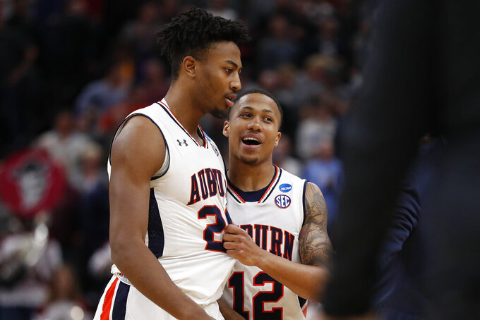 Auburn forward Anfernee McLemore, left, and guard J'Von McCormick (12) celebrate after winning a first round men's college basketball game against the New Mexico State in the NCAA Tournament Thursday, March 21, 2019, in Salt Lake City. (AP Photo/Jeff Swinger)