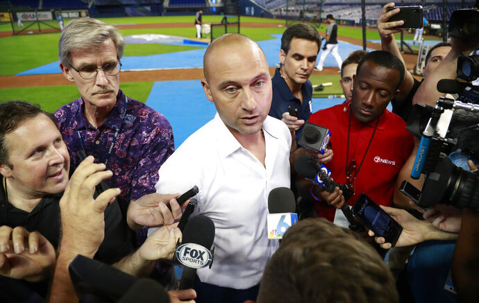 FILE - In this June 10, 2019, file photo, Miami Marlins CEO Derek Jeter, center, talks with members of the media before the start of a baseball game between the Marlins and the St. Louis Cardinals, in Miami. Derek Jeter watched the first pitch on opening day from the owner's box next to the dugout, but within a few innings retreated to a more secluded location and rarely returned to his field-level seat during the season. Alas, from whatever vantage point, Jeter's team looked bad. (AP Photo/Wilfredo Lee, File)
