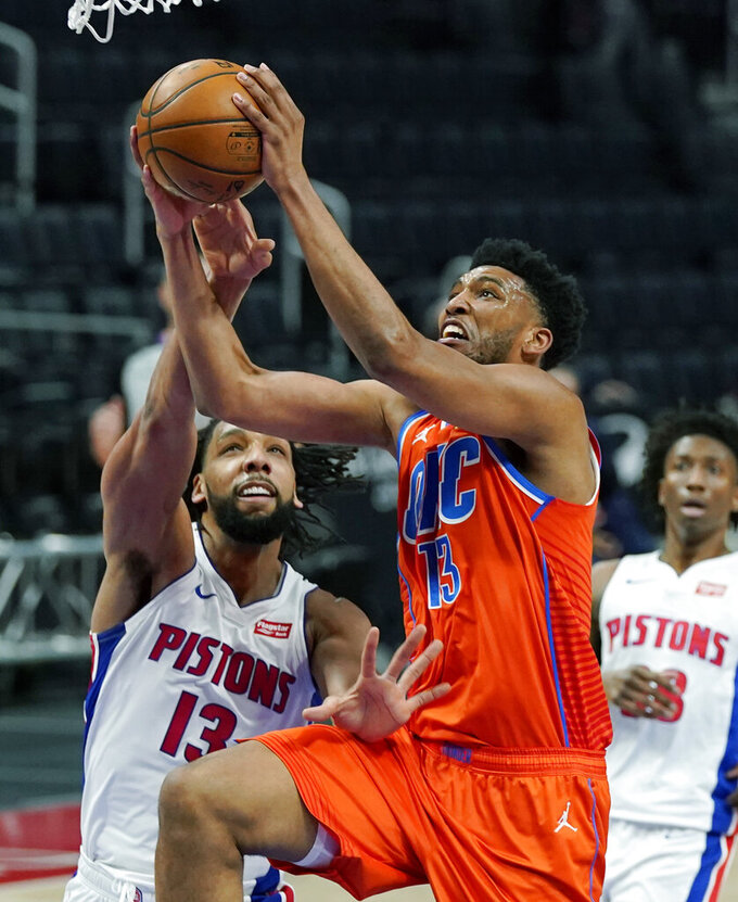 Oklahoma City Thunder center Tony Bradley (13) makes a layup as Detroit Pistons center Jahlil Okafor (13) defends during the first half of an NBA basketball game, Friday, April 16, 2021, in Detroit. (AP Photo/Carlos Osorio)