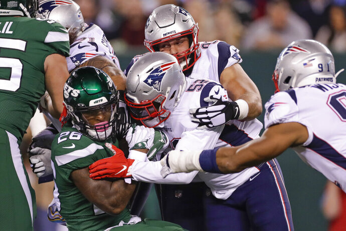 New England Patriots outside linebacker Elandon Roberts (52) tackles New York Jets' Le'Veon Bell (26) during the first half of an NFL football game Monday, Oct. 21, 2019, in East Rutherford, N.J. (AP Photo/Adam Hunger)