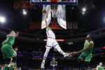 Philadelphia 76ers' Ben Simmons, center, goes up to shoot against Boston Celtics' Marcus Smart (36) as Daniel Theis (27) looks on during the second half of an NBA basketball game, Thursday, Jan. 9, 2020, in Philadelphia. (AP Photo/Matt Slocum)