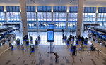 Passengers move about a spacious Terminal B of New York's LaGuardia Airport, Wednesday, March 24, 2021, in New York. The terminal was opened on June 13, 2020 as part of a challenging architectural plan that is expanding the airport on no more acreage than before. (AP Photo/Craig Ruttle)
