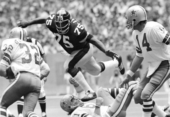 FILE - In this Oct. 8, 1972, file photo, Pittsburgh Steelers left tackle Joe Greene (75) takes a short cut over Dallas Cowboys guard Blaine Nye (61) to put a sudden halt on Cowboys' Walt Garrison (32) during a football game in Irving, Texas. The beginning of the Pittsburgh Steelers dynasty of the 1970s can be pinpointed to the drafting of defensive lineman Joe Greene in 1969. (AP Photo/Fred Kaufman, File)