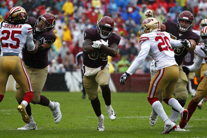 Washington Redskins running back Wendell Smallwood, center, rushes the ball in the first half of an NFL football gameagainst the San Francisco 49ers, Sunday, Oct. 20, 2019, in Landover, Md. (AP Photo/Alex Brandon)