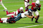 Philadelphia Eagles quarterback Jalen Hurts (2) dives in to the end zone for a touchdown as Arizona Cardinals strong safety Budda Baker and cornerback Patrick Peterson (21) defend during the second half of an NFL football game, Sunday, Dec. 20, 2020, in Glendale, Ariz. (AP Photo/Rick Scuteri)
