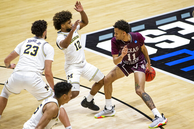 Texas Southern's Jordan Gilliam (11) dribbles behind his back to move around Michigan's Mike Smith (12) and Michigan's Brandon Johns Jr. (23) during the second half of a first-round game in the NCAA men's college basketball tournament, Saturday, March 20, 2021, at Mackey Arena in West Lafayette, Ind.  (AP Photo/Robert Franklin)