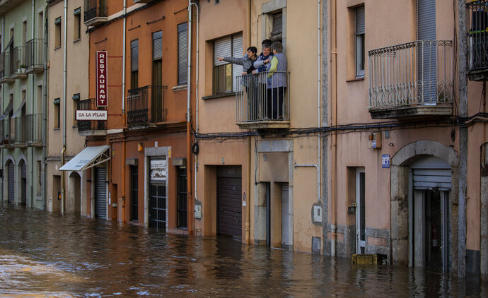 FILE - In this Thursday, Jan. 23, 2020 file photo, people stand on a balcony during flooding in Girona, Spain. A storm caused rivers to overflow and sea waters to inundate vast agricultural areas in eastern Spain. On Thursday, Feb. 13, 2020, scientists from the U.S. National Oceanic and Atmospheric Administration said the previous month was the hottest January on record since experts began keeping temperature tallies in 1880. (AP Photo/Emilio Morenatti)