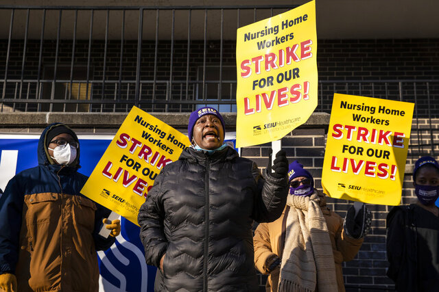 Annette Delaney, 54, a travel escort at Ambassador Nursing & Rehabilitation Center in Albany Park, leads a rally of striking Infinity Healthcare Management workers outside the Northwest Side facility, Monday, Nov. 23, 2020. Nearly 700 workers walked off the job Monday at 11 Infinity facilities across the Chicago area, saying they won't return until the company offers them higher wages and safer working conditions. (Ashlee Rezin Garcia/Chicago Sun-Times via AP)