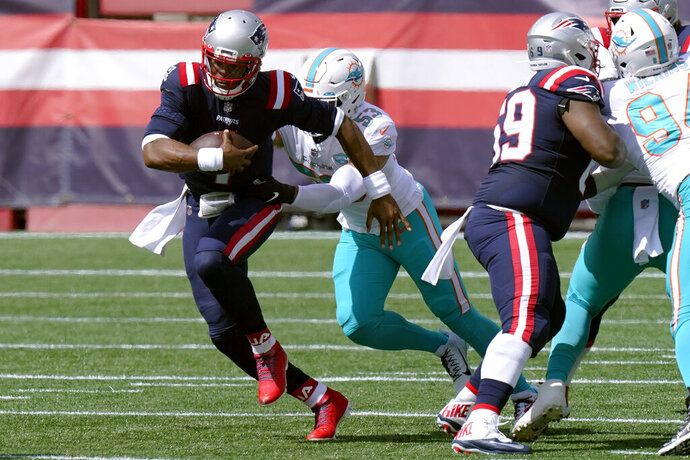 New England Patriots quarterback Cam Newton, front, runs from Miami Dolphins linebacker Kyle Van Noy (53)in the first half of an NFL football game, Sunday, Sept. 13, 2020, in Foxborough, Mass. (AP Photo/Steven Senne)